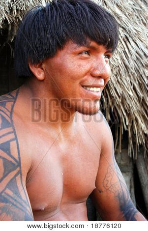 KAMAYURA VILLAGE, BRAZIL - MAY 18: The Kamayura is a threatened Indian tribe of under 400 people. A man sitting at doorway of a hut on May 18, 2008, in Kamayura village.