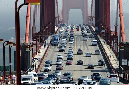 Zoom of heavy traffic on Golden Gate Bridge, connecting San Francisco to Marin County, warm air rising from road and cars in the front