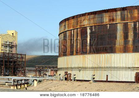 Rusty oil storage tank in a bleak industrial area