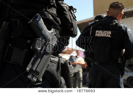 Closeup of a handgun of Mexican federal police forces maintaining order in the violent border city of Ciudad Juarez