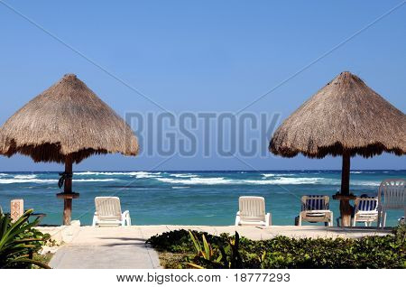 Two palapas on a tropical beach with empty beach chairs