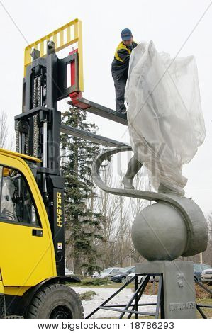 MOSCOW - APRIL 07: Worker unwraps statue of Yuri Gagarin  on April 07, 2011 in Moscow, Russia. Yuri Gagarin is the first Russian cosmonaut.