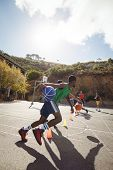 Basketball players practicing dribbling drill  in basketball court outdoors poster