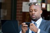 stock photo of goatee  - A good looking African American business man works on his laptop or netbook computer with a smart phone in his hands - JPG