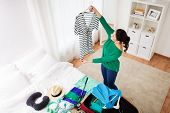 tourism, people and luggage concept - happy young woman packing travel bag at home or hotel room poster