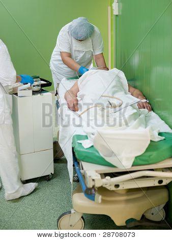 Enfermera prepara el paciente para la operación