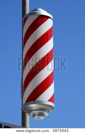 Striped Barbers Pole Set Against Bright Blue Sky