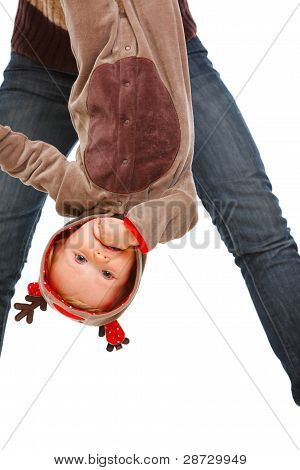 Mother Holding Cute Baby In Costume Of Santa Claus's Reindeer Upside Down