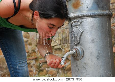 Girl drinking water from a fountain