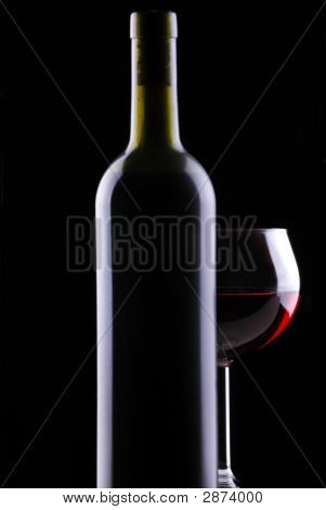 Red Wine Glass In Behind Bottle