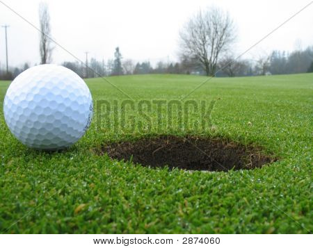 Golf Ball Beside Hole
