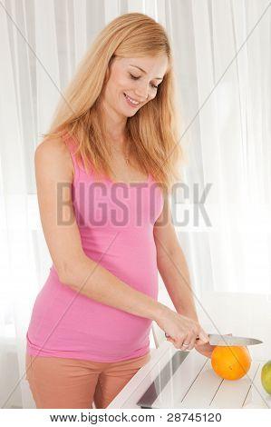 Pregnant Woman Cutting Orange