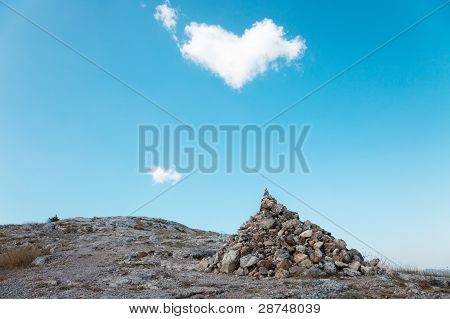 A Pile Of Stones And A Passing Cloud In The Shape Of Heart