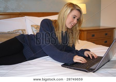 Girl sitting on her bed communicating with friends