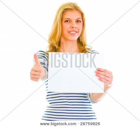 Smiling Teen Girl Holding Blank Paper And Showing Thumbs Up