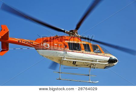Orange And White Helicopter Overhead