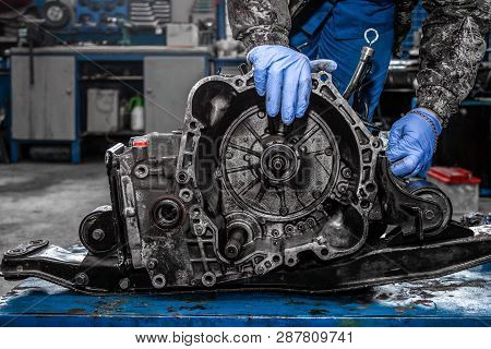 poster of A Close-up Of A Young Man Repairman In A Working Uniform Of Cars Is Repairing An Automatic Gearbox O