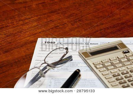 Calculadora de pluma de formas fiscales y vidrios en escritorio