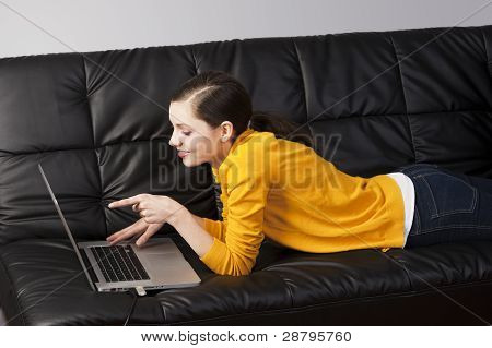 Girl On Sofa With Laptop, She Watches The Display