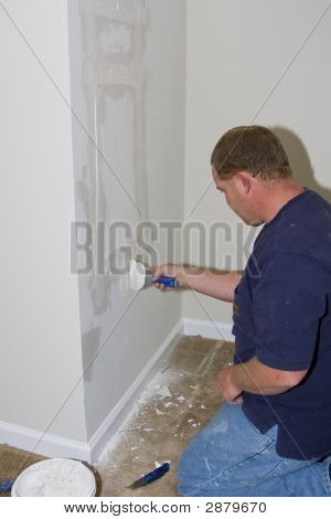 Painter Repairing Large Hole In Sheetrock