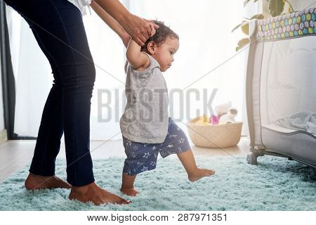 Babys first steps holding mothers