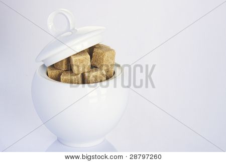 white sugar-bowl with brown sugarcubes