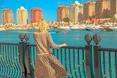 Tourism In Qatar. Blonde Elegant Woman At Marina Walkway Looks At Porto Arabia, The Pearl-qatars Mai poster