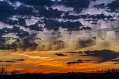 The Setting Sun Paints A Cloudy Sky With Intense Colors And A Dramatic Beauty. poster
