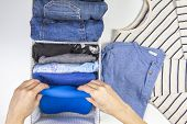 Woman Hands Tidying Up Kids Clothes In Basket. Vertical Storage Of Clothing, Tidying Up, Room Cleani poster