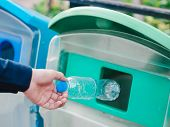 Closeup Of Man Hand Throwing Empty Plastic Water Bottle In Recycling Bin. poster