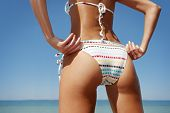 image of bum  - close up outdoor shot of young woman in white bikini sunbathing at sea shore - JPG