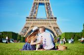 Romantic Couple Having Picnic On Grass With Wine And Fruits Near The Eiffel Tower In Paris poster