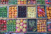 Set Of Fruit Is Sold In Tray From Street Vendor. Fruit Trays For Sale Of Mangoes, Pomegranates, Bana poster