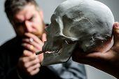 Man Smoking Cigarette Near Human Skull Symbol Of Death. Harmful Habits. Smoking Cause Health Damage  poster