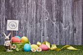 Colored easter eggs, easter rabbit and flowers lying on a green grass on a grey wooden  background w poster