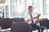 Front view of Caucasian male doctor sitting on chair and using digital tablet in conference room poster