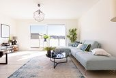 Modern living room with designer sofa and coffee table. Window with view. Nobody inside poster