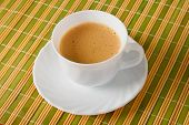 foto of scum  - Cup of coffee with scum on straw napkin - JPG