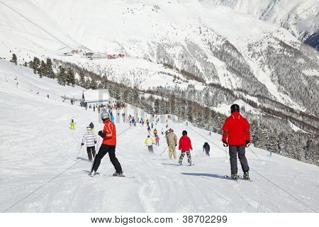 Skiers go down from hill to ski lift