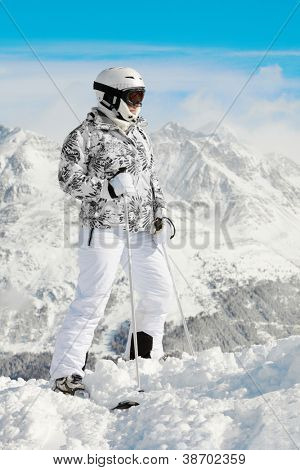 Young woman in ski suit stands on background of mountains and blue sky