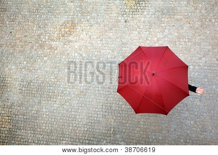 Businesswoman hidden under umbrella and checking if it's raining