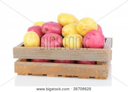 A wooden crate full of red and white potatoes on a white background with reflection. Horizontal Format.