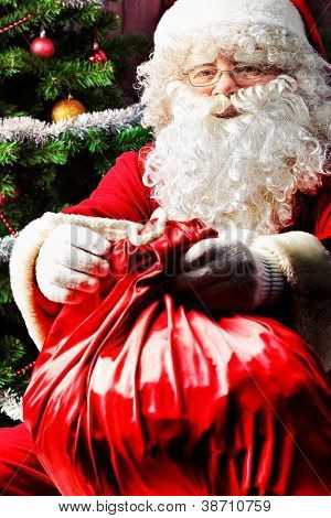 Santa Claus sitting with presents over Christmas background.