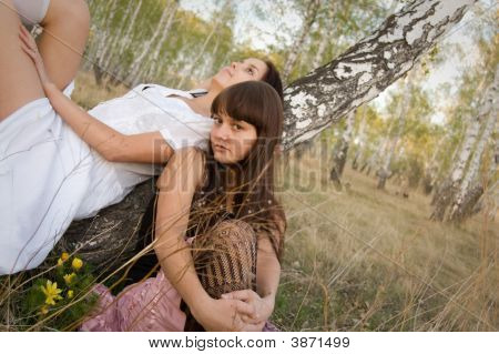 Two Girls Sit Near Birch