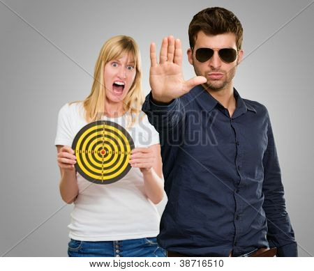 Man Making Hand Stop And Afraid Woman Holding Dartboard On Gray Background