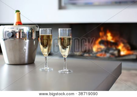 Closeup of champaign glasses set by fireplace