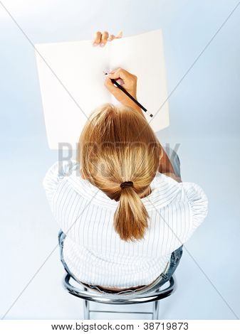 Student girl passing exams in classroom, cute schoolgirl drawing in textbook, sweet teenager writing letter on blank paper, young female sitting on chair rear view, education concept, back to school