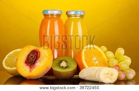 Delicious multifruit juice in a bottle and fruit next to it on yellow background