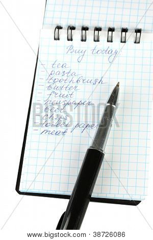 shopping list in a notebook on white background close-up