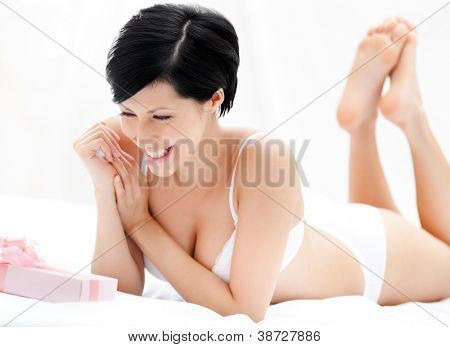 Woman in underwear finds a surprise in bed, white background